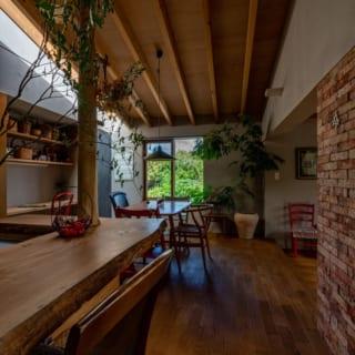 キッチンの中心には家族で伐採し磨いた柱が。テーブルも同様に樹齢200年の杉の木から作り出したもの