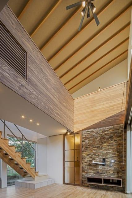 吹き抜けの天井は、垂木を現しにすることでより高さを出した。アクセントウォールは、石版を一枚一枚手貼りしたこだわりの品