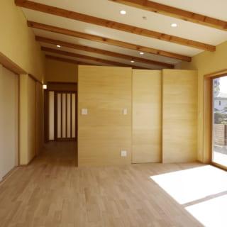 リビングからキッチン方向を見る。キッチンはボックス状に囲い、また出入口に扉を設け来客時などは目隠しできる。天井の梁は構造部材。梁の下に天井板を設けないため天井が上がり、キッチンの上部にも視線の抜けをつくったことで奥行きを感じる開放的な空間に仕上がった