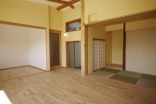 リビング、南側から北側の中庭方向を見る。右の和室の床柱は以前の家のもの。和室からも、障子を開けて中庭を楽しむことができる。リビングに面した掃き出し窓の上部に換気のための窓を設けた
