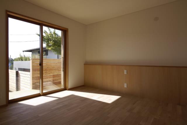 主寝室。窓の先には縁側があり、ここからも庭に出られる。窓から見えるのは、建て替え前の家から残したモミジの木