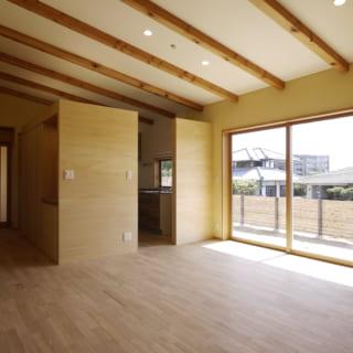 勾配天井により空間に伸びやかさがあり、シンプルな設えのリビングは、どんな意匠の家具でもしっくりくるおおらかさがある。大きな窓の外には縁側を設けた。いつか家庭菜園がしたい、というご要望から縁側付近の庭は畑作業ができるよう計画した