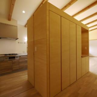 玄関側からキッチンを見る。撮影点のすぐ後ろにご主人の趣味室があり、わざわざリビングへ行くことなくキッチンにアクセスできるようにした。通路側には大容量の収納を設け、LDK全体の使い勝手を向上させた