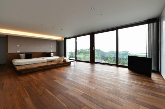 ブラックウォルナットの床材で落ち着いた雰囲気をもつ寝室からも、富士山の景色が楽しめる。ベッドは牧野嶋さんが手掛けたオリジナル