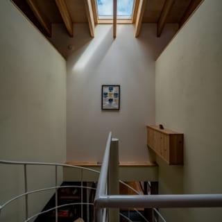 2階へとつながる螺旋階段はトップライトからの陽が差し込み明るい。雨の日は、ワイヤーを張ることで、洗濯物を干すスペースにもなるという