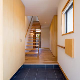 瓦調のタイルを用いた住居部分の玄関。タイルは床材のオークとの相性を考えて清さんが提案したもの