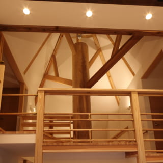 1階リビングから大樹状の柱を見上げる。柱から出た梁と三角錐の梁により大きな木のように見える。柱は太く立派で、N邸のシンボルツリーとしてふさわしい。柱が乾燥によって割れるのを防ぐため、あらかじめ背割りをし、その割った部分にも目立たないよう木材を入れた