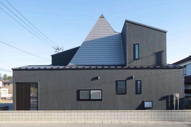 北側の外観。縦格子の箇所は駐輪場。屋内にある大樹状の柱の三角錐をできるだけ生かした外観は、遠くからも目を引く。お子さまたちにとっても自慢の家となった