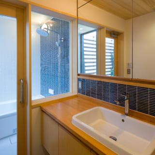 バスルーム。お客様の要望でホテルのような仕様とし、ガラス張りの洗面室とつなげている