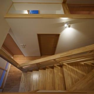 2階のステージ状の階段から1階を見る。脱衣室や浴室の天井のくり抜き部分から視線が抜け、空間が広く感じられる。蒸気も浴室から上に抜けるため冬は加湿に役立つ。人の目より高い位置から撮影しているためくり抜きがわかるが、普段の生活動線で浴室まわりが見えることはない