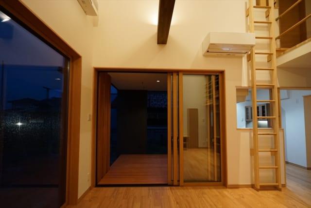 1階リビングからその先のウッドデッキまでを見る。ウッドデッキはリビングとフラットに繋げ、また天井を設けたことで、リビングの延長のように感じられる。遊べる家にすべく、垂直方向にも回遊性を持たせたN邸。梯子を上ると子ども室の前に出る
