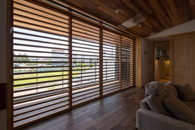 リビングの木製サッシは春と夏はフルオープンで使い、蒸し暑い夏はルーバーの網戸で日差しを遮りながら風を取り入れられるようになっている