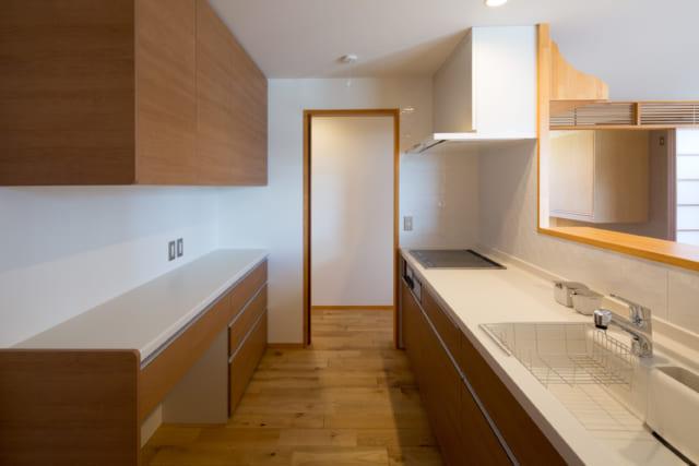 真っ白が良いという要望に沿ってつくられたキッチン。レンジフードも合わせて白く仕上げている。木製の扉の先は小屋裏収納