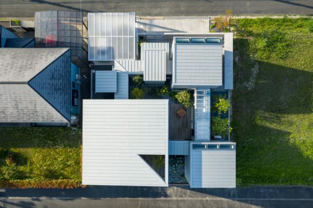 敷地の中に大小5つの正方形の棟を配し、正方形の回廊でつなぐ構成