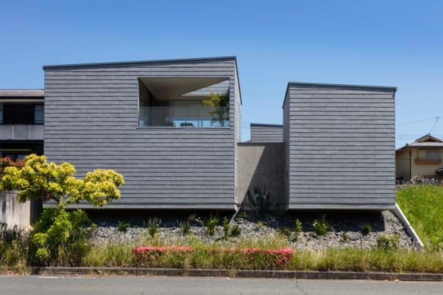 グレーのスレートで覆われ、重厚感をもつY邸。敷地の傾斜に対して建物を浮かせるイメージで軽やかさを出した