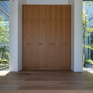 高く広々とした玄関。中庭を背に、リビングと個室をつなぐ回廊の役割も