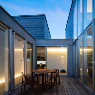 中庭を囲むように、LDK、個室、子供部屋の建物が配置され回廊でつながる
