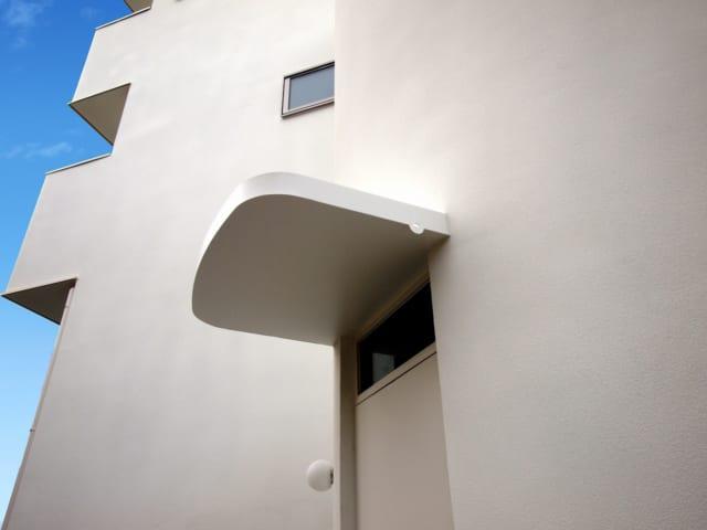 法規の制約の中で内部空間をできるだけ広くとるために、玄関まわりはR壁に。カドが丸い庇もかわいい。庇は上面が箱のようになっていて雨水がたまる仕組み。その雨水を壁際の小さな穴から落とすという岡本さんのアイデアだ。おかげで竪樋が不要になり、玄関まわりはすっきり