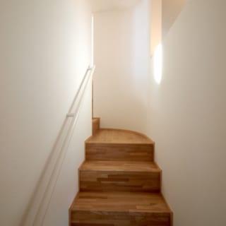 5層のフロアの2層目から上に向かう階段。突き当りのコーナー部分はR壁にし、行き止まり感を緩和