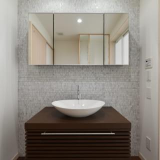 1階洗面室。水がかかる可能性がある奥の壁面には大理石のタイルを使用。ハイセンスな高級感がある