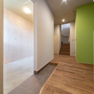 1階玄関。スキーがご趣味というお施主さまのご要望から、玄関脇にはメンテナンス用のスキールーム(写真左)を配置した。湿気がたまるのを防ぎたいスキールームやクローゼットルームの壁面は、無塗装の北海道産トドマツ合板を用いた。珪藻土のように調湿作用があり結露しにくい