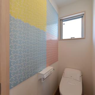 1階トイレ。お客様も使用するトイレには、カラフルなパズル柄のタイルを貼った
