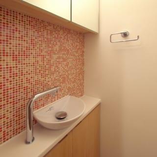 玄関トイレの手洗いはモザイクタイルと木で造作。白と木目が基調の邸内でアクセント的に映える空間