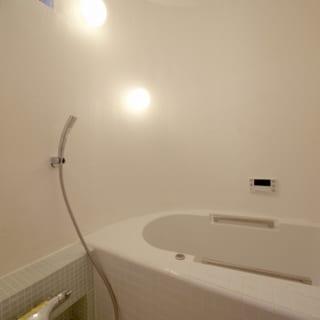 建ぺい率の関係でR壁にした浴室は在来工法でつくったオリジナル。塗り壁とタイルでナチュラルな仕上がりに
