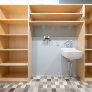 1階洗面脱衣室。中央が洗濯機スペース。洗濯機まわりが全て収納で、棚の高さも可動式と機能的な空間だ