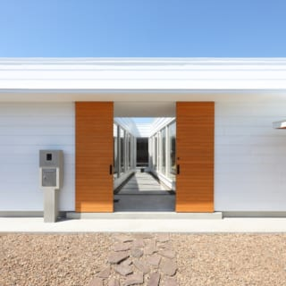 白が好きなKさんのために、白で統一された建物の正面。木の扉を開けると居住空間の間に配された台形のテラスが現れる