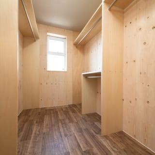 1階、クローゼットルーム。家族全員分の着替えを収納するためハンガーパイプを張り巡らせている