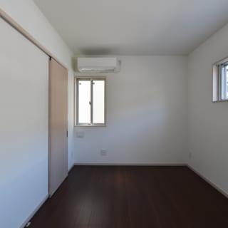 1階寝室。画像右の北側の窓は、道路からの視線を考慮し高めの位置に設けた。横長のフォルムは外観のアクセントにもなっている。左の2つの引き戸はウォークインクローゼットに続く。将来1階のみで暮らすことを想定し、衣服の収納はここに集めた