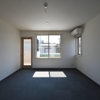 2階居室(図面BR2)の南側を見る。南には庭があり、隣家との距離が離れているため大きく窓を取った。窓の左の扉から物干し場やロフトへの階段にアクセスできる。扉は物干し場からの日光を部屋の中にも届けられるよう、すりガラスとした