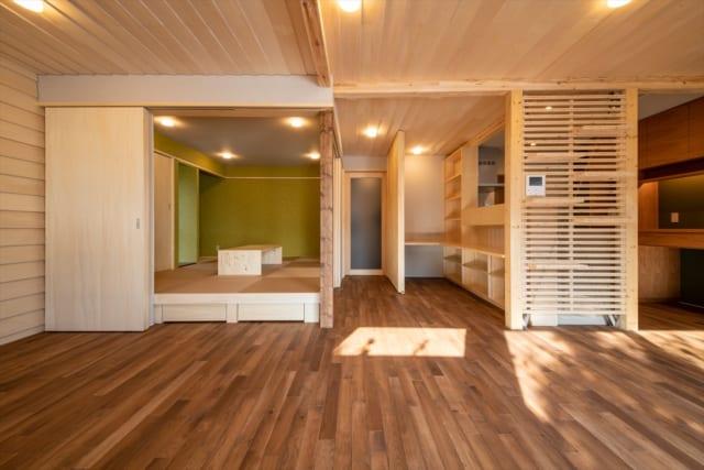 リビングからキッチン、ワークスペース、和室を見る。キッチンからはルーバーを通してリビングまで目が届くようにした。一段床を上げることで空間に変化をもたらしている和室は、引き戸を占め完全に独立した空間にすることも可能。天井だけでなく壁も下見板張りとし、趣ある空間に