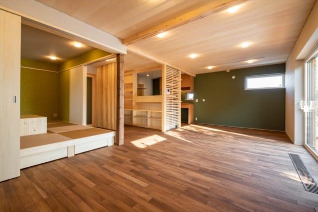 LDK及び和室はワンルーム空間を緩やかに仕切り構成。床下は基礎断熱とし、温水暖房ヒーターを設けている。床下の温風を窓脇のガラリから昇らせ、コールドドラフトを防いだ。写真奥の壁面や、和室の壁面はお施主さまが選ばれた色。色味の異なるグリーンがアクセントになっている
