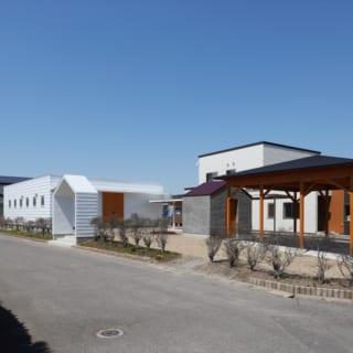 駐車スペース側から見たK邸。奥に建てられた真っ白なK邸の外観が、青森の青い空に映える