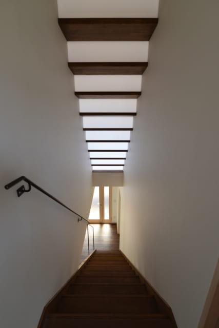 上部の2階からロフトへの階段はポリカーボネート板の蹴上から光が抜けるように計画。1階までを明るくする