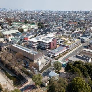 上空からの眺め。写真中央、広々とした屋上庭園のあるレンガ色の建物が『リバービレッジ杉並』。写真右手前の緑が妙正寺公園。左手前が妙正寺川。周辺は、緑に包まれた低層の住宅地
