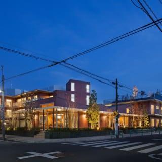 交差点からの眺め。2階、3階へと徐々に高くなるデザインの効果で、大規模施設ながら軽やかな印象に。写真中央にあるガラス張りのところがカフェ。カフェとその奥の地域交流スペースの屋根は稜線を思わせる起伏がつけられ、立体感のある建築美が引き立つ