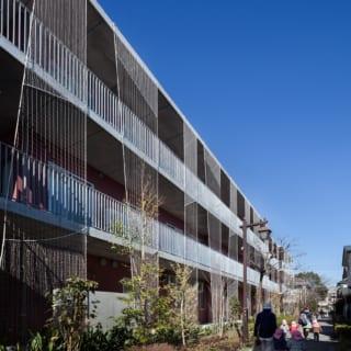 外壁にはツル植物を這わせた短冊状のネットを設置。ネットはリズミカルな動きをつけて並べている
