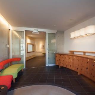 施設へのエントランスロビーは、コンクリート打ち放しや間接照明を取り入れた洗練された空間。館内の家具は全て、カフェの家具と同じデザイナーの作品