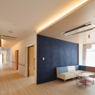 光あふれる談話スペースにも、ユニットのテーマカラーが使われている。居室への通路は中廊下。この廊下を挟んで居室が並んでいる