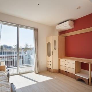 居室の1つ。居室は全て中庭もしくは外周部に面した窓があり、窓越しの景色に開放感があって気持ちがいい。オリジナルのデザイン家具やアクセントカラーの壁も取り入れられ、住まいとして快適に暮らせる空間になっている