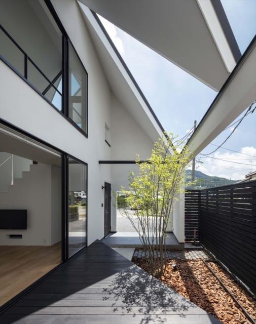 中庭にかかる屋根は、三角形の開口。構造的安定、玄関部分の雨除けなどいくつもの要素をもたせた。中庭のデッキも三角形
