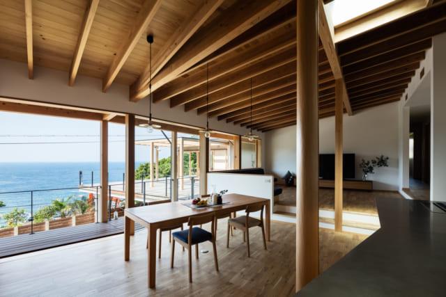 家の軸として、海が一番美しく見えるところにLDKを配置した。海側の窓は框を隠したつくり。まるで柱しかないように見え、海の景色がより迫力あるものに感じられる。週末住宅のため、留守中に割れる心配がないよう窓ガラスは10mm厚のガラスを採用した